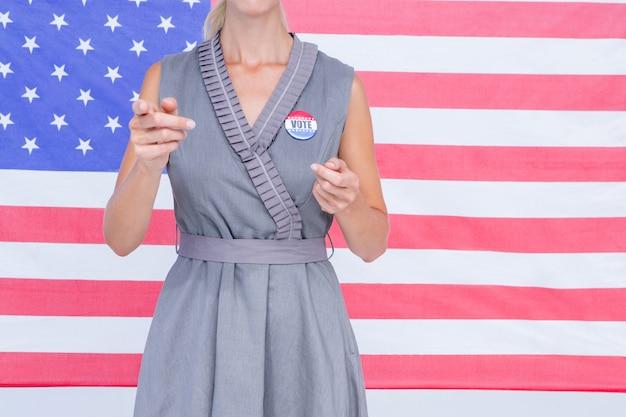 Femme blonde gesticulant devant drapeau américain avec badge