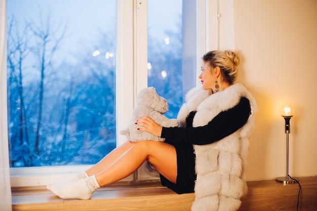 Femme blonde en gilet de fourrure jouant avec jouet hippo assis sur le rebord de la fenêtre.