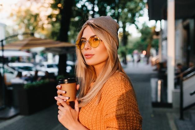 Femme blonde glamour en lunettes de soleil rondes transportant une tasse de café et à la voiture en face de la rue ombragée
