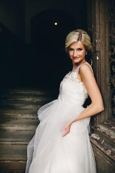 Femme blonde habillée comme une jeune mariée se penchant sur une porte