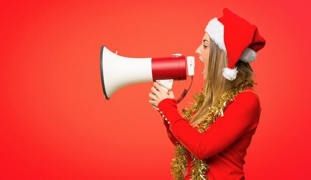 Femme blonde habillée pour les vacances de noël criant à travers un mégaphone