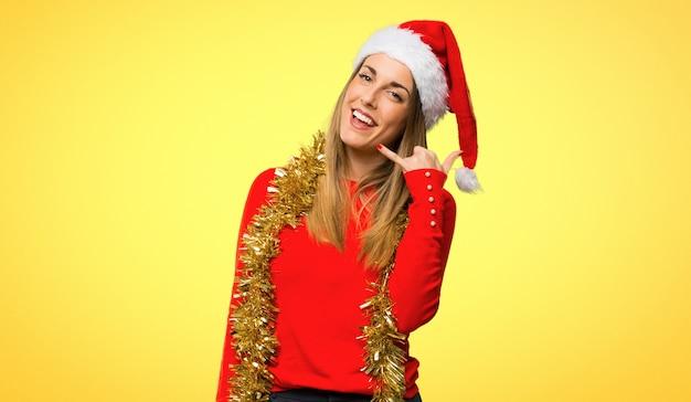 Femme blonde habillée pour les vacances de noël, geste de téléphone