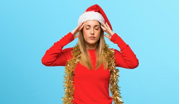 Femme blonde habillée pour les vacances de noël malheureuse avec quelque chose.