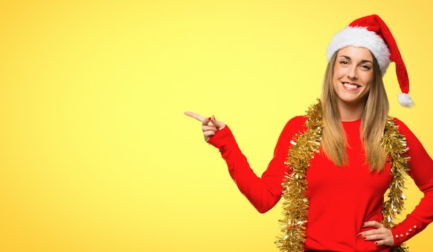 Femme blonde habillée pour les vacances de noël, pointant le doigt vers le côté