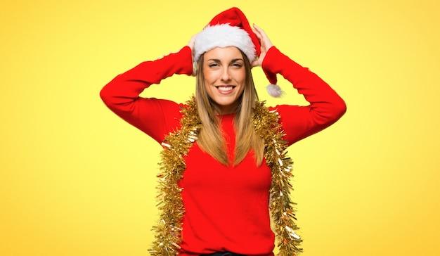 Femme blonde habillée pour les vacances de noël prend les mains sur la tête