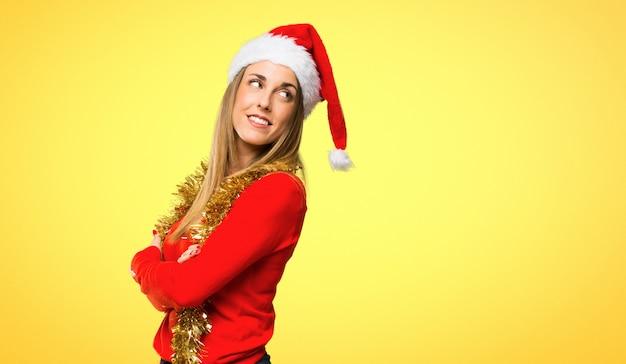 Femme blonde habillée pour les vacances de noël, regardant par-dessus l'épaule avec un sourire