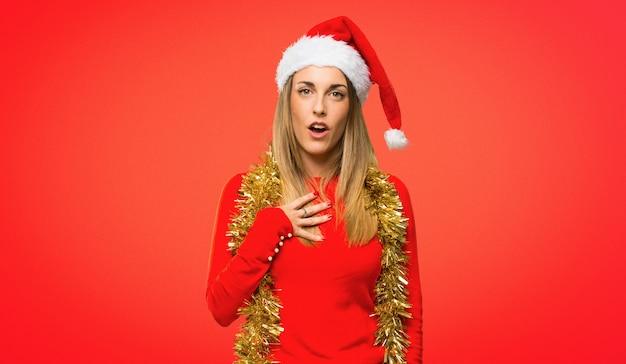 Femme blonde habillée pour les vacances de noël, surprise et choquée.