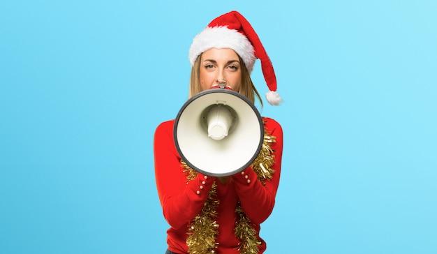 Femme blonde habillée pour les vacances de noël tenant un mégaphone sur fond bleu