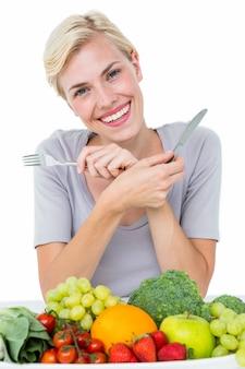 Femme blonde heureuse assis au-dessus de la nourriture saine