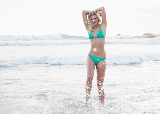 Femme blonde heureuse en bikini vert posant en regardant la caméra