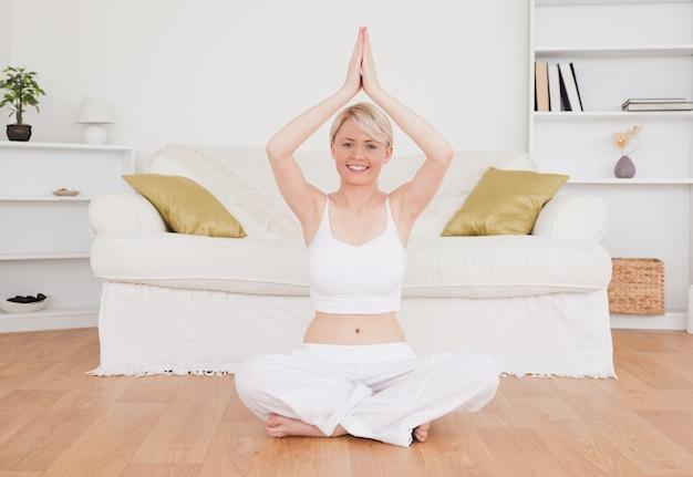 Femme blonde heureuse, pratiquant le yoga