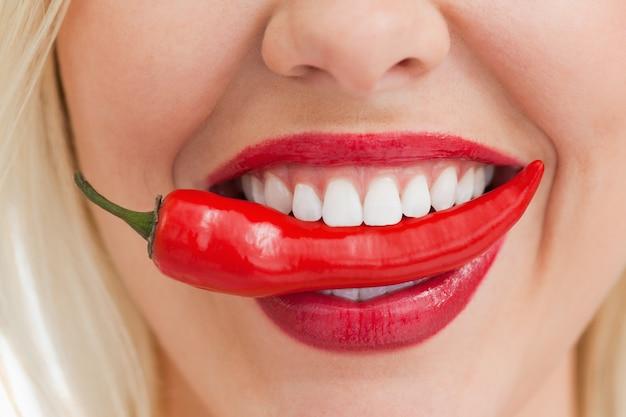 Femme blonde heureuse tenant un piment avec sa bouche