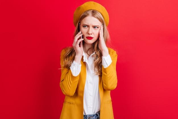 Femme blonde irritée en béret jaune, parler au téléphone. fille caucasienne en veste tenant le smartphone sur le mur rouge.