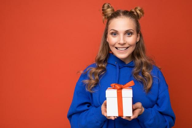 Femme blonde isolée sur mur de fond coloré portant une tenue à la mode tous les jours tenant une boîte-cadeau et regardant la caméra.