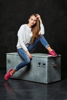 Femme blonde en jeans et baskets roses assis sur une boîte à colis