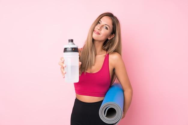 Femme blonde jeune sport sur rose isolé avec une bouteille d'eau de sport et un tapis
