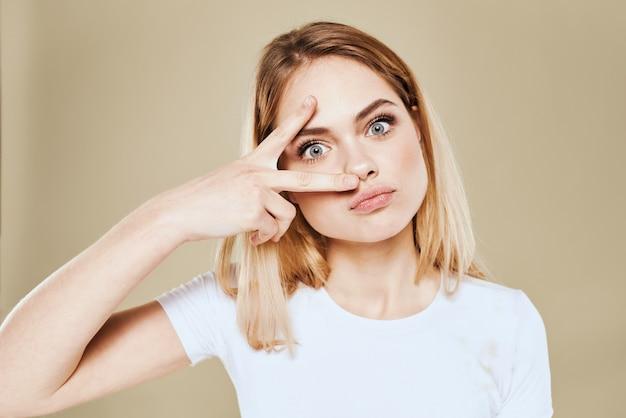Femme blonde joyeuse dans un t-shirt blanc fait des gestes avec ses émotions de la main fond beige.