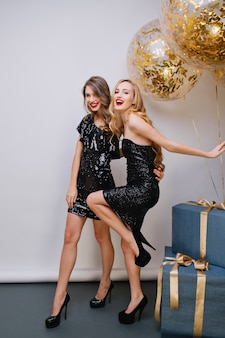 Femme blonde joyeuse danse drôle à côté des coffrets cadeaux bleus et regardant avec le sourire. portrait intérieur de deux jolies filles passer du temps ensemble pendant la fête d'anniversaire.