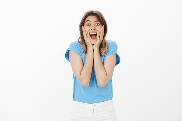 Femme blonde joyeuse et excitée à la surprise, bonne nouvelle