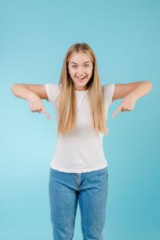 Femme blonde joyeuse, pointant les doigts isolé sur bleu