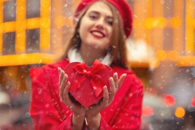Une femme blonde joyeuse porte un béret rouge et un manteau tenant une boîte-cadeau en forme de coeur pendant les chutes de neige. espace pour le texte