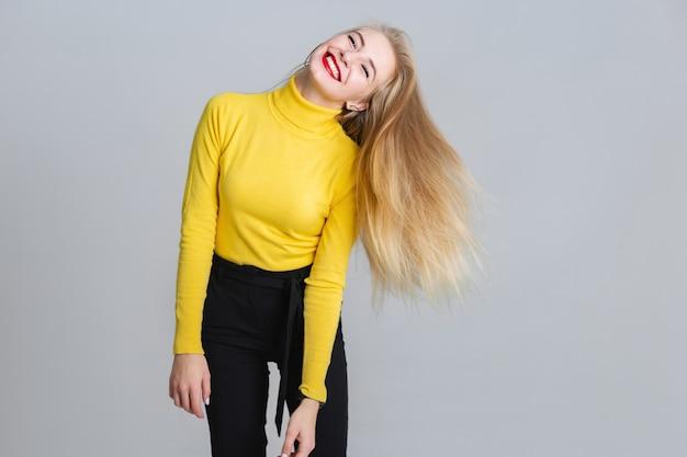 Femme blonde joyeuse s'amuser dans le studio.
