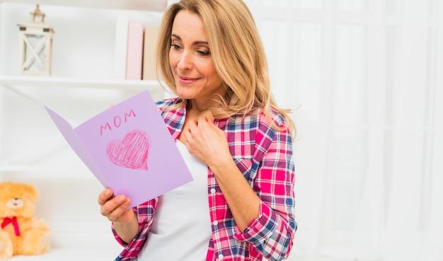 Femme blonde lisant une carte de voeux avec inscription de maman