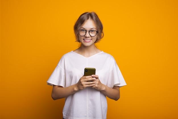 Femme blonde avec des lunettes bavardant sur mobile et sourire sur un mur jaune portant un t-shirt blanc