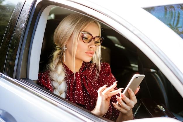 Une femme blonde à lunettes dans un chemisier rouge est assise derrière le volant et résout les affaires à l'aide du téléphone.