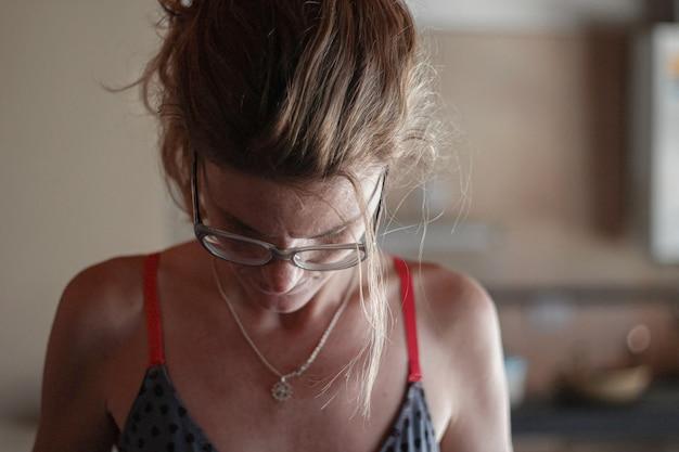 Femme blonde avec des lunettes portant un soutien-gorge noir et regardant vers le bas