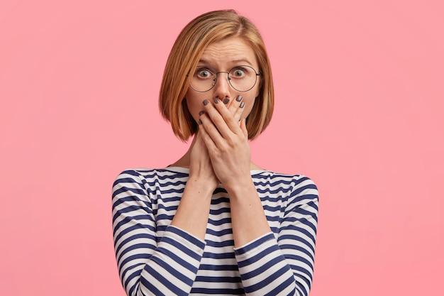 Femme blonde à lunettes rondes et chemisier rayé