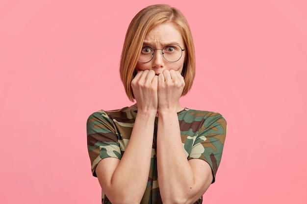 Femme blonde à lunettes rondes et t-shirt camouflage