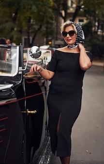 Femme blonde à lunettes de soleil et en robe noire près de la vieille voiture classique vintage.