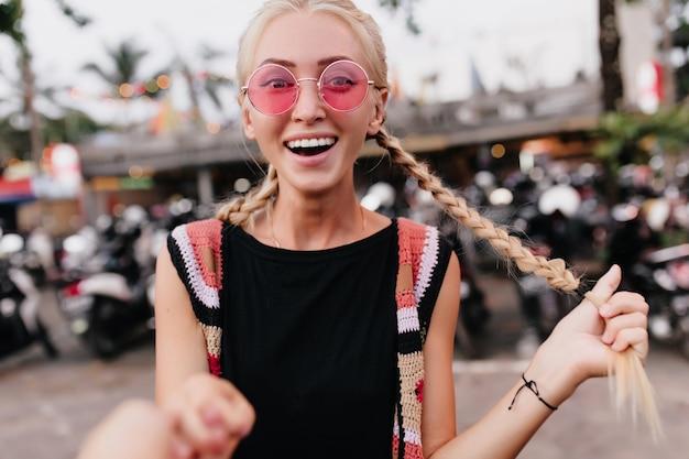 Femme blonde à lunettes de soleil roses posant avec un sourire surpris. femme en riant avec des tresses exprimant l'étonnement sur fond de rue flou.
