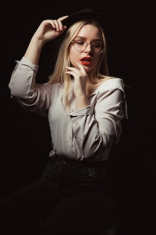 Femme blonde luxueuse à lunettes et chapeau, vêtue d'une chemise aux épaules nues, posant avec une lumière dramatique au studio