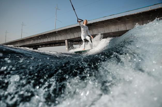Femme blonde en maillot de bain blanc à cheval sur le wakeboard tenant une corde sur le pont
