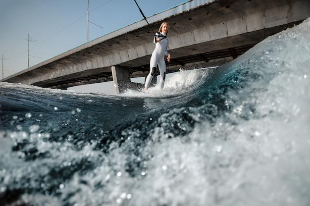 Femme blonde en maillot de bain blanc debout sur le wakeboard tenant une corde sur le pont