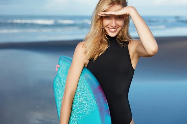 Femme blonde en maillot de bain avec planche de surf sur la plage