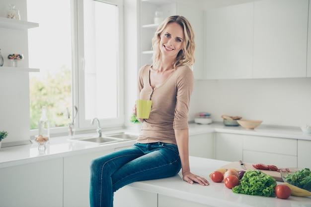 Femme blonde à la maison dans la cuisine avec des légumes
