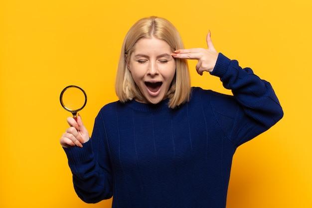 Femme blonde à la malheureuse et stressée, geste de suicide faisant signe des armes à feu avec la main, pointant vers la tête