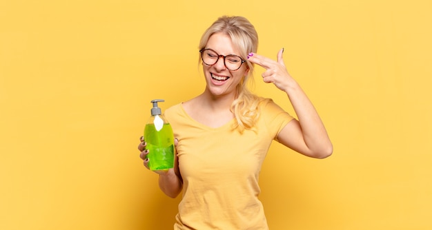 Femme blonde à la malheureuse et stressée, geste de suicide faisant signe de pistolet avec la main, pointant vers la tête