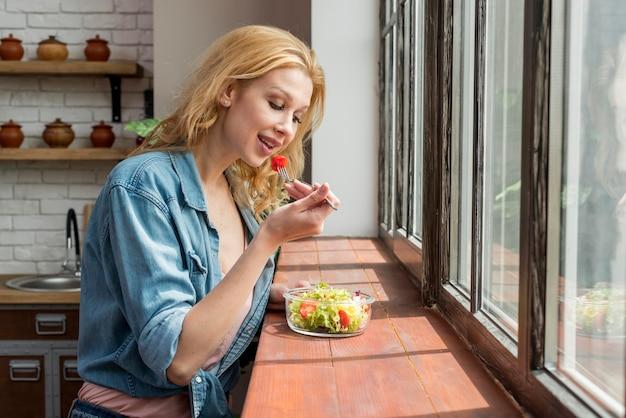 Femme blonde mangeant une salade