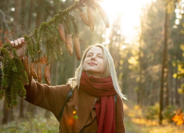 Femme blonde en manteau et écharpe rouge détient une branche de pin avec des cônes dans une forêt