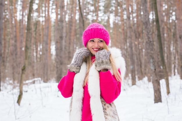 Femme blonde marchant dans un chapeau rose et des pulls en bois d'hiver