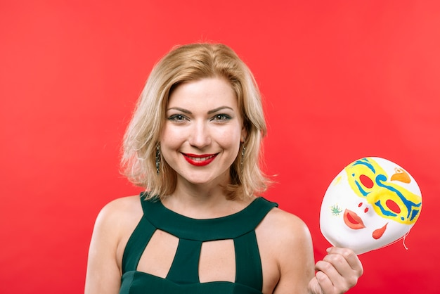 Femme blonde avec masque de carnaval à la main