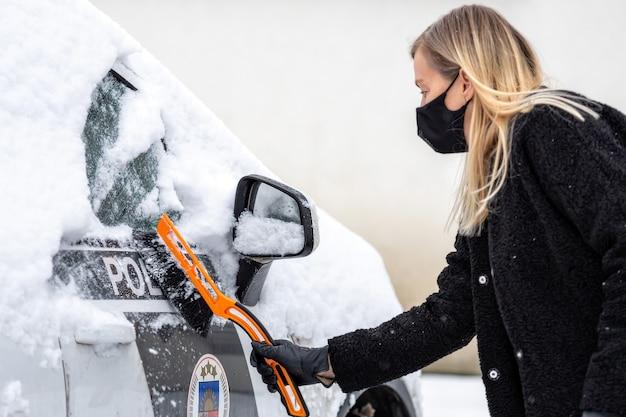 Une femme blonde en masque facial avec une raclette nettoie la neige d'une voiture de police