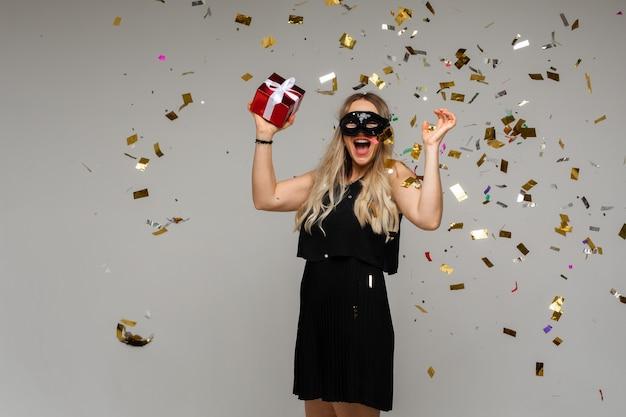 Femme blonde en masque fantaisie et robe avec cadeau.