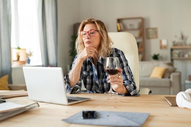 Femme blonde mature en chemise à carreaux ayant un verre de vin rouge assis par table devant un ordinateur portable et la communication en ligne