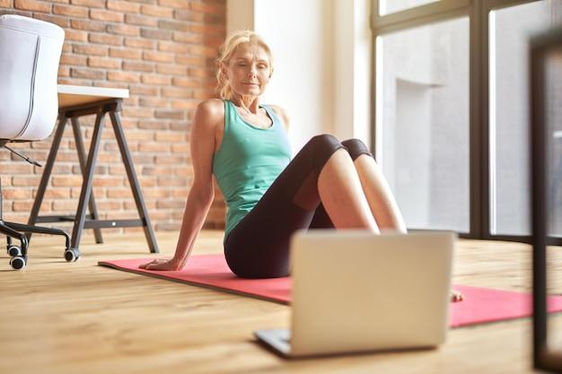 Femme blonde mature ciblée en tenue de sport assise sur le sol et regardant un cours de yoga vidéo en ligne