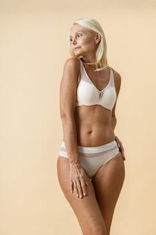 Femme blonde mature avec un corps en forme en sous-vêtements blancs regardant de côté tout en posant isolé sur beige
